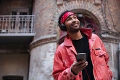 Portret uśmiechnięty afro amerykański mężczyzna słucha muzyka Obrazy Stock