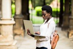 Portret uśmiechnięty amerykanin afrykańskiego pochodzenia uczeń robi pracie domowej outdoors używa laptop dla badania Pozytywny z zdjęcie stock