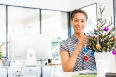Portret uśmiechnięty amerykanina urzędnik dekoruje choinki w offfice Zdjęcie Royalty Free