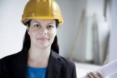 Portret uśmiechnięty architekt trzyma staczający się w górę projekta indoors w hardhat, zakończenie Fotografia Royalty Free