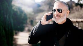 Portret uśmiechnięty atrakcyjny mężczyzna jest ubranym czarną kurtkę i opowiada przy smartphone podczas gdy wydający czas w miast Zdjęcie Stock