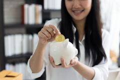 Portret uśmiechnięty azjatykci młoda kobieta chwyta prosiątka bank i moneta obrazy royalty free
