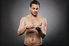Portret uśmiechnięty bez koszuli mężczyzna używa aftershave płukankę Zdjęcie Royalty Free