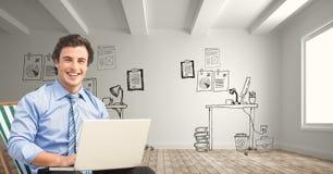 Portret uśmiechnięty biznesmen używa laptop przeciw biurowemu rysunkowi fotografia royalty free