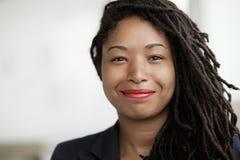 Portret uśmiechnięty bizneswoman z dreadlocks, kierowniczym i ramionami, Fotografia Royalty Free