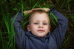Portret uśmiechnięty chłopiec lying on the beach na zielonej trawie Zdjęcie Royalty Free