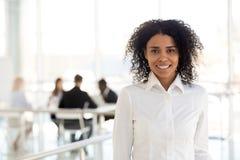 Portret uśmiechnięty czarny żeński pracownik pozuje dla obrazka zdjęcie royalty free