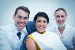 Portret uśmiechnięty dentysta i asystent z żeńskim pacjentem Obrazy Royalty Free