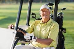 Portret uśmiechnięty dojrzały mężczyzna jeżdżenia golfa powozik obraz royalty free