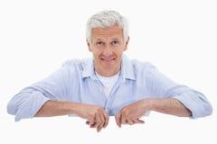 Portret uśmiechnięty dorośleć mężczyzna pozycję za pustym panelem Fotografia Royalty Free
