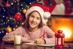 Portret uśmiechnięty dziewczyny writing list Santa Zdjęcia Stock