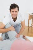 Portret uśmiechnięty fizyczny terapeuta egzamininuje kobiety nogę Obraz Royalty Free