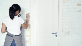 Portret uśmiechnięty kobieta pracownik maluje ścianę z cegieł w domu lub mieszkaniu zbiory