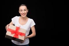 Portret uśmiechnięty kobiety mienia prezent w rękach i patrzeć kamera na czerni Fotografia Royalty Free