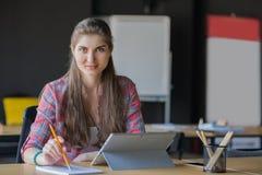 Portret Uśmiechnięty kobiety Writing w notatniku podczas gdy Pracujący na laptopów lndoors Obraz Stock