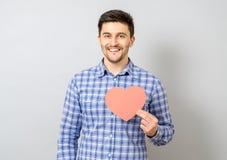 Portret uśmiechnięty mężczyzna mienia czerwieni papieru serce Obraz Royalty Free