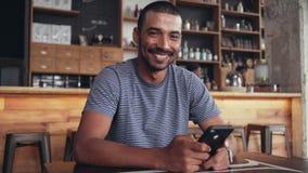 Portret uśmiechnięty mężczyzna używa mądrze telefon w kawiarni zbiory wideo