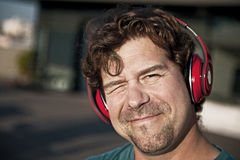 Portret uśmiechnięty mężczyzna w czerwonych hełmofonach Zdjęcia Royalty Free