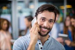 Portret uśmiechnięty męski kierownictwo opowiada na telefonie komórkowym Zdjęcia Royalty Free