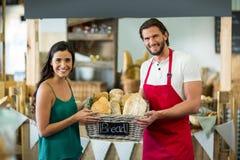 Portret uśmiechnięty męski personel i kobieta trzyma kosz baguettes przy kontuarem Obraz Royalty Free