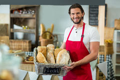 Portret uśmiechnięty męski personel trzyma kosz baguettes przy kontuarem Zdjęcia Stock