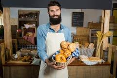Portret uśmiechnięty męski personel trzyma kosz chleb przy kontuarem Zdjęcia Royalty Free