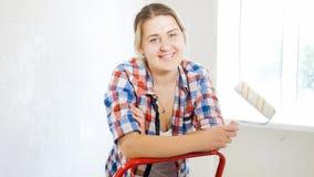 Portret uśmiechnięty młodej kobiety mienia farby rolownik i patrzeć w kamerze Fotografia Royalty Free