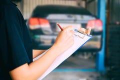 Portret uśmiechnięty młody żeński mechanik sprawdza na samochodzie wewnątrz obrazy royalty free