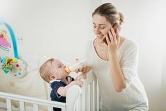 Portret uśmiechnięty młody bizneswoman opowiada telefonem i karmieniem jej mały dziecko syn zdjęcie stock