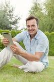 Portret uśmiechnięty młody człowiek używa pastylka komputer w parku Zdjęcia Stock