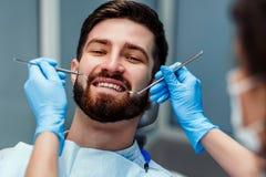 Portret uśmiechnięty młody człowiek z dentystą trzyma stomatologicznych narzędzia przy kliniką Zamyka w g?r? widok obraz stock