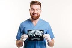 Portret uśmiechnięty młody męski lekarz medycyny pokazuje radiograph Zdjęcie Royalty Free
