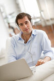 Portret uśmiechnięty młody przystojny facet z laptopem używać słuchawki zdjęcie stock