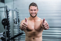 Portret uśmiechnięty mięśniowy mężczyzna patrzeje kamerę z kciukiem up Obraz Stock
