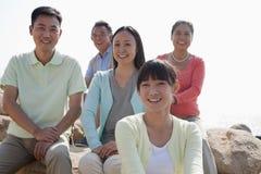 Portret uśmiechnięty multigenerational rodzinny obsiadanie na skałach outdoors, Chiny Obraz Royalty Free