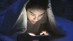Portret uśmiechnięty nastoletniej dziewczyny lying on the beach pod koc i używać telefonem komórkowym zbiory