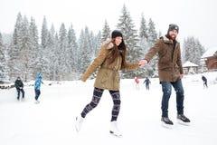 Portret uśmiechnięty pary jazda na łyżwach outdoors Zdjęcie Stock