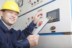 Portret uśmiechnięty pracownika mienia schowek i sprawdzać kontrola w benzynowej roślinie, Pekin, Chiny fotografia stock