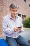 Portret uśmiechnięty profesor używa telefon komórkowego w kampusie zdjęcie royalty free