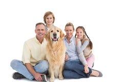 Portret uśmiechnięty rodzinny obsiadanie wraz z ich psem Obrazy Royalty Free