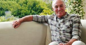 Portret uśmiechnięty starszego mężczyzna obsiadanie na kanapie w żywym pokoju zbiory wideo