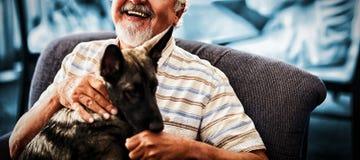 Portret uśmiechnięty starszego mężczyzna obsiadanie z szczeniakiem na krześle obraz royalty free