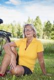 Portret uśmiechnięty starszy kobiety obsiadanie przy parkiem z bicyklem Obraz Stock