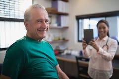 Portret uśmiechnięty starszy męski pacjent z żeńskim terapeuta trzyma cyfrową pastylkę Zdjęcia Royalty Free