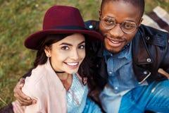 Portret uśmiechnięty wielokulturowy pary obsiadanie na trawie w zdjęcie stock