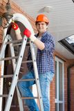 Portret uśmiechnięty złotej rączki pięcie na stepladder naprawiać latarnie uliczne Obraz Stock