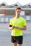 Portret używa jego mądrze telefon dla młody sportowiec słucha muzykę podczas sprawności fizycznej trenuje outdoors, Obrazy Stock