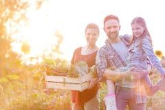 Portret u?miechni?ta rodzina z warzywami w skrzynce przy gospodarstwem rolnym zdjęcia stock