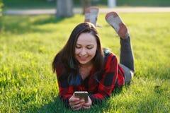 Portret u?miechni?ty kobiety lying on the beach na zielonej trawie i u?ywa? outdoors smartphone obraz royalty free