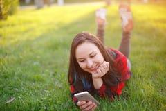 Portret u?miechni?ty kobiety lying on the beach na zielonej trawie i u?ywa? outdoors smartphone obrazy stock